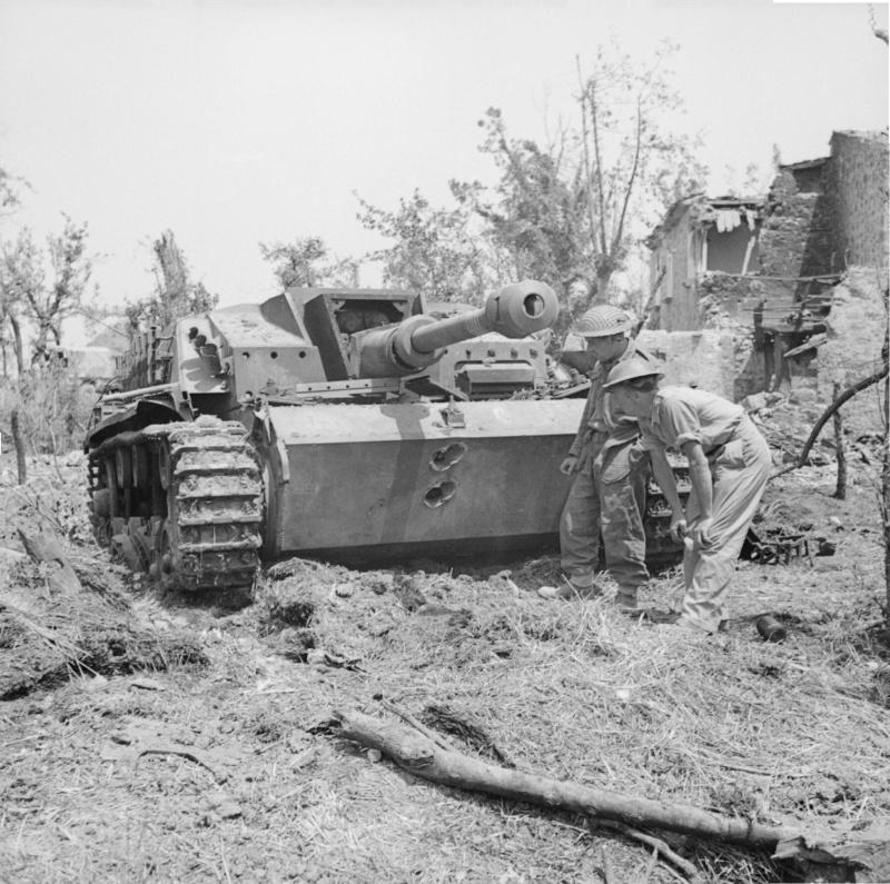 Британские солдаты смотрят на пробоины в лобовой броне немецкой САУ StuG III ausf G