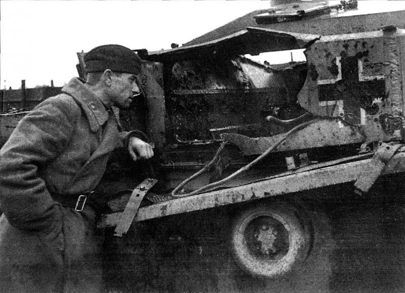 Советский солдат осматривает подбитое немецкое штурмовое орудие StuG III Ausf.F. Пролом в броне позволяет заглянуть внутрь самоходки.