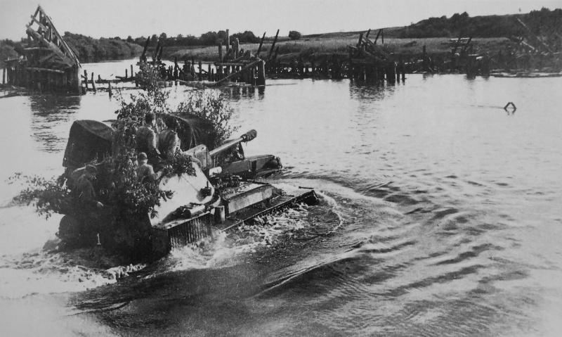 Советская САУ СУ-76М переправляется через реку рядом с разрушенным мостом