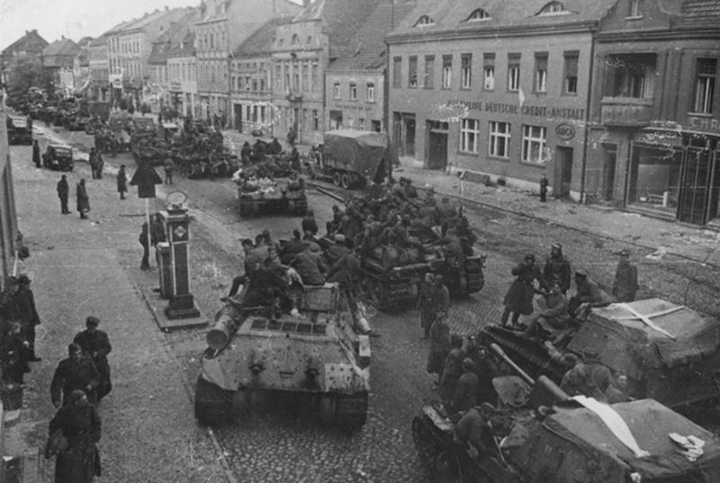 Колонна советской бронетехники на улице немецкого города. На фотографии танки Т-34-85 и САУ СУ-76М