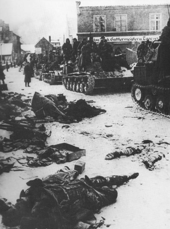 САУ СУ-76М с солдатами на броне из состава 10-го танкового корпуса 5-й гвардейской танковой армии 2-го Белорусского фронта и тела немецких солдат на улице Мюльхаузена (ныне польский город Млынары)