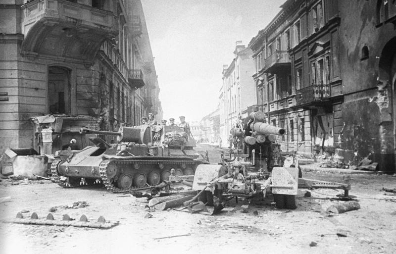 Советская САУ СУ-76М проезжает мимо разбитого 88-мм немецкого зенитного орудия (8,8 cm FlaK 18) в Вильнюсе