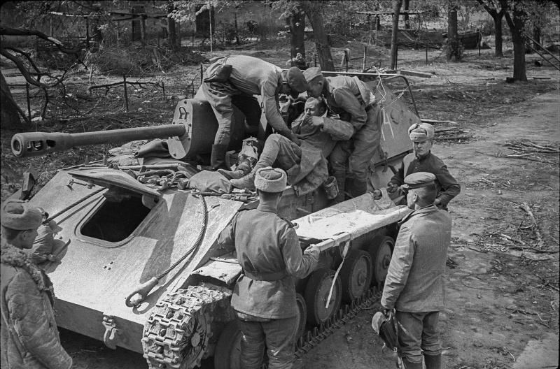 Раненого советского бойца перекладывают с САУ СУ-76М на носилки под Берлином