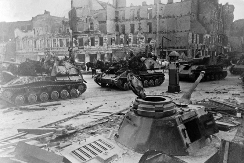 Колонна советских самоходок СУ-76 проезжает мимо закопанного немецкого танка Pz.Kpfw.IV, использовавшегося как ДОТ на улице Берлина