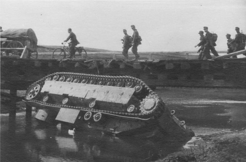 Немецкие егеря 97-й горно-пехотной дивизии проходят мимо советского среднего танка Т-28, упавшего с моста через речку Восушка