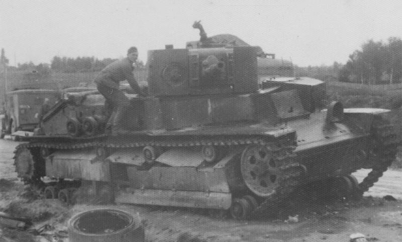 Немецкие солдаты рассматривают подбитый и сгоревший советский экранированный танк Т-28 выпуска 1939 года с пушкой Л-10