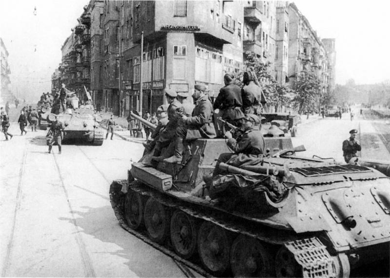 Колонна советских самоходных артиллерийских установок СУ-85М с солдатами на броне проезжает по улице Берлина