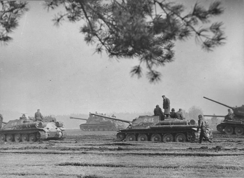 Колонна советских самоходно-артиллерийских установок СУ-85М из 7-го гвардейского танкового корпуса 3-й гвардейской танковой армии с пехотой на броне в ожидании марша