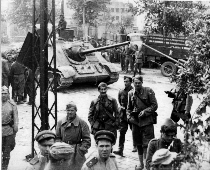 Советские и сербские военнослужещие в Белграде. Позади них советская САУ СУ-85.