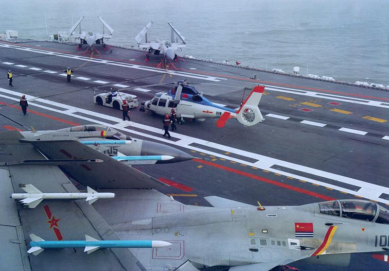 На палубе авианосца «Ляонин», 2015-2016 год. На технических позициях пришвартованы истребители J-15, по угловой палубе перемещают вертолёт Z-9