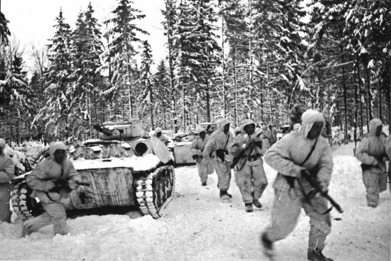 Танковый десант одной из частей 1-й Гвардейской мотострелковой Московской дивизии и колонна легких танков Т-40 в зимнем лесу во время битвы за Москву.
