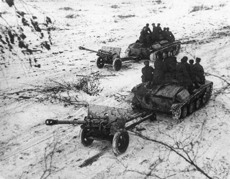 Расчеты 76,2-мм дивизионных орудий передвигаются на броне танков Т-60.