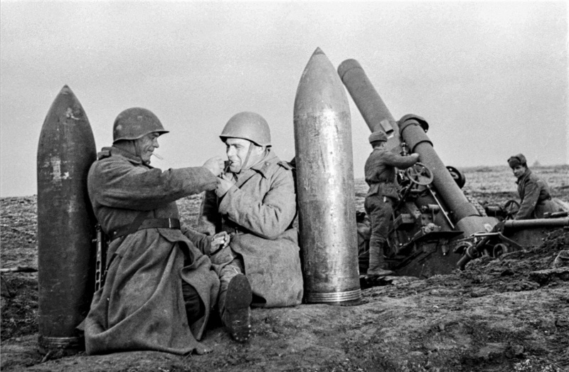 Красноармейцы-артиллеристы расчета 280-мм мортиры образца 1939 года Бр-5 отдыхают у снарядов.