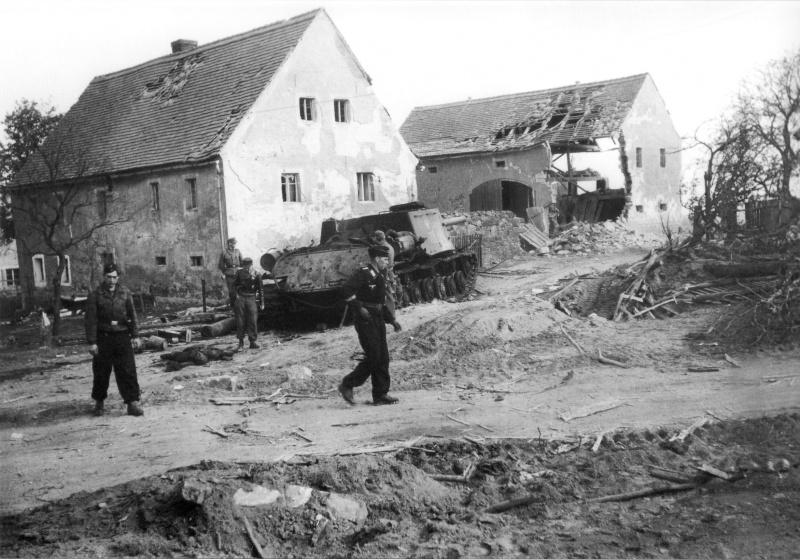 Среди разрушенных зданий стоит подбитая самоходная установка ИСУ-122 советского производства с польским орлом на броне