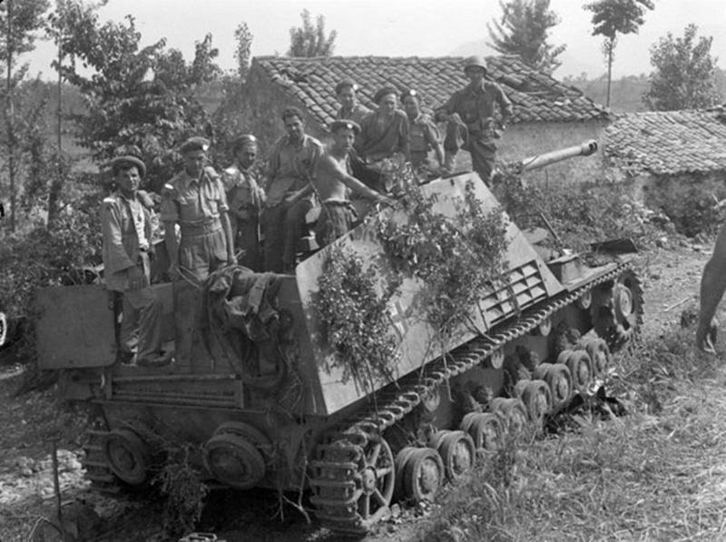Солдаты полка «Вестмистер» 5-й канадской танковой бригады (Westminster Regiment, 5th Canadian Armoured Brigade) в боевом отделении немецкой САУ «Насхорн» (Sd.Kfz. 164 «Nashorn»), подбитой из противотанкового гранатомета PIAT на улице итальянской деревни Понтекорво