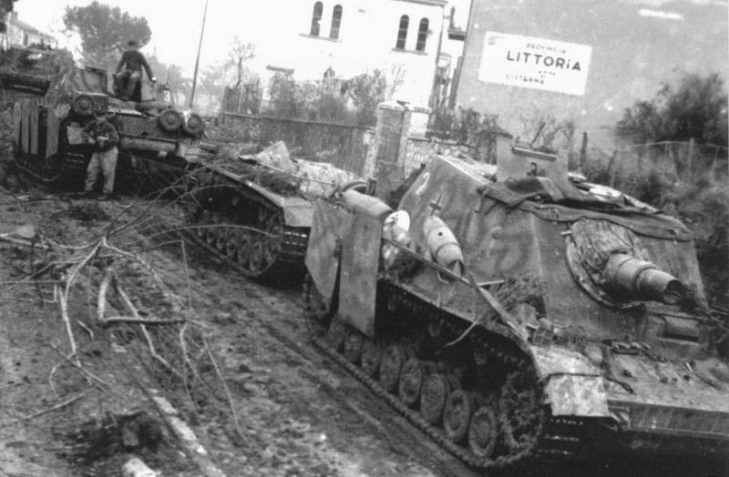 Немецкие самоходные орудия Штурмпанцер IV «Бруммбар» (15 cm Sturmpanzer IV «Brummbar») из 216-го штурмового батальона (Stu.Pz.Abt. 216) на дороге в итальянском городе Чистерна (Cisterna di Latina). Между САУ стоит транспортировщик боеприпасов Munitionspanzer III