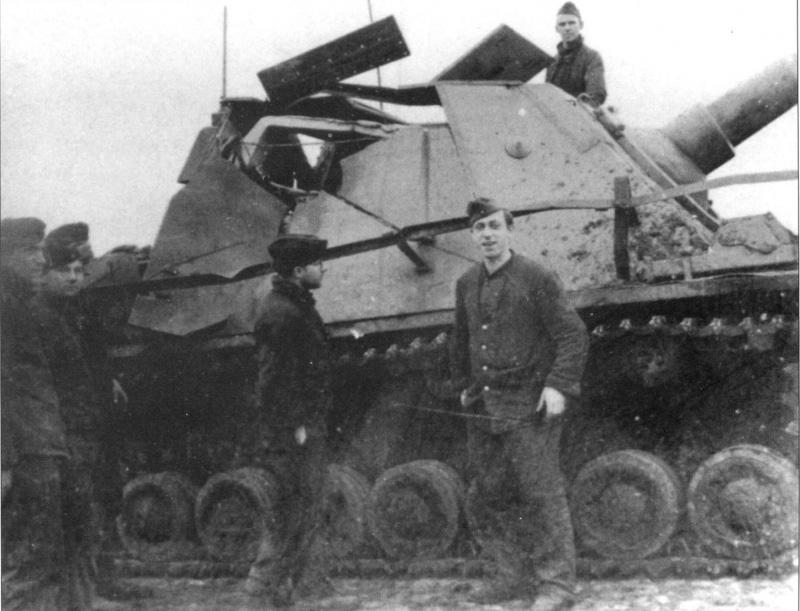 Немецкие солдаты у подбитого <a href='https://arsenal-info.ru/b/book/2435493365/3' target='_self'>штурмового орудия</a> Sturmpanzer IV «Бруммбар» (15 cm Sturmpanzer IV «Brummbar»). Самоходка повреждена точным попаданием в рубку, экипаж погиб