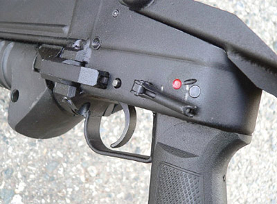 С обеих сторон ствольной коробки магазинного гранатомета ГМ-94 над пистолетной рукояткой управления огнем смонтирован флажковый предохранитель