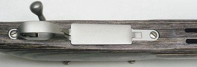 Нижняя пластина выполнена из лёгкого сплава в виде цельной детали; образует защитную скобу спуска и крепление для откидывающейся вниз крышки магазина.