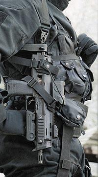 Германский спецназовец из группы GSG-9 с пистолетом-пулеметом МР7А1, пристегнутым к системе ношения с возможностью быстрого извлечения оружия