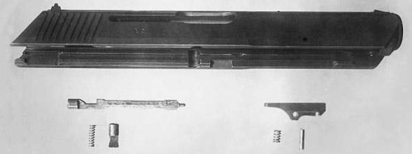 Затвор пистолета CZ 513 в разобраном виде. 1 – корпус затвора, 2 – ударник, 3 – стопор ударника с пружиной, 4 – выбрасыватель, 5 – пружина и ось выбрасывателя. Принцип запирания канала ствола остался прежним. Запирающие ролики входили в полукруглые пазы «а» на затворе