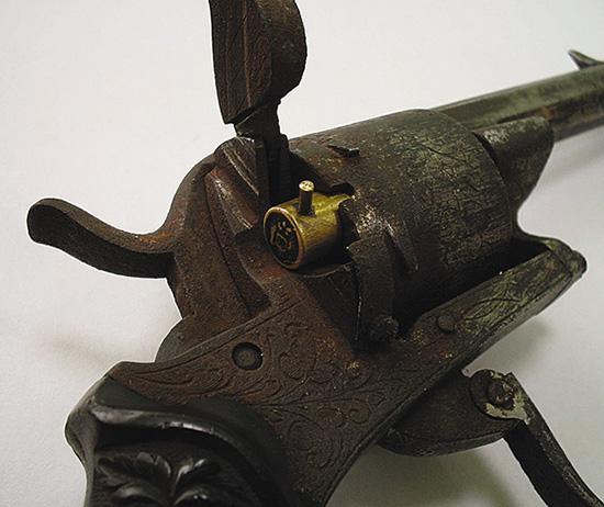 ДВЕРЦА БАРАБАНА. Сегодня откидывающаяся дверца барабана кажется неотъемлемой частью старинных револьверных конструкций. Действительно, практически все старейшие револьверы под унитарные шпилечные патроны «с дверцей». Нажимается кнопка защелки, дверца откидывается, и патроны по одному вкладываются в каморы барабана, экстрагируются стреляные гильзы также по одной. Уже в середине XIX века появились переламывающиеся и раздвигающиеся револьверные системы, которые позволили уйти от неудобной, пусть и надежной, схемы «с дверцей». В России наиболее известной подобной архаичной конструкцией является револьвер системы Наган. На основе этой безнадежно устаревшей еще во второй половине XIX века системы в СССР долгое время выпускалось армейское и спортивное оружие, а сегодня — малокалиберный карабин.