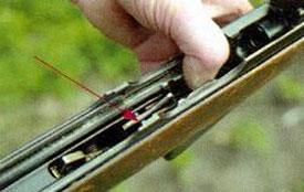 Двуплечий подпружиненный рычаг при наличии патронов в магазине работает как отражатель, а после израсходования всех патронов - как задержка затвора.