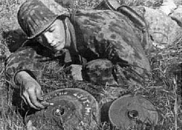 немецкий сапер в момент опускания в гнездо мины взрывателя