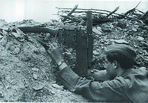 Германский снайпер ведет прицельный огонь из карабина Маузер К98к, смонтированного в приспособлении для стрельбы из-за укрытий. Восточный фронт. Харьков. 1943 год
