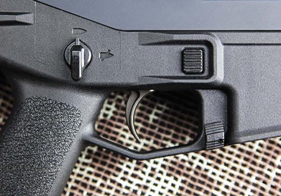 Управление винтовкой — полностью двухстороннее. Кнопка выброса магазина (а) и рычаг предохранителя (б) находятся там же, что и у AR-15. А затворная задержка переместилась в основание спусковой скобы (в)