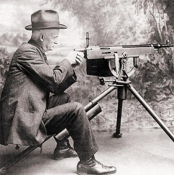 Джон Мозес Браунинг у своего пулемета