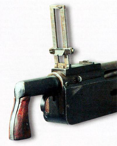 Затыльник пулемета «Кольт» с рукояткой и спусковым крючком. С правой стороны ствольной коробки виден замыкатель затыльника. Рамка прицела поднята