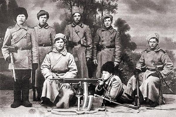 Студийное фото времен Гражданской войны в России: солдаты армии А. Колчака позируют на фоне пулемета «Кольт». 1919 г.