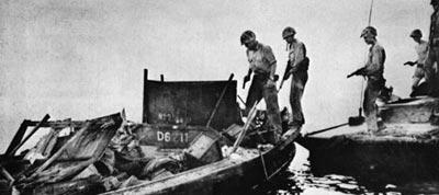 Американские солдаты с пистолетами Кольт М 1911А1 осматривают японскую трофейную лодку. 1944 год