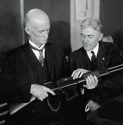 Джон Мозес Браунинг (слева) с автоматической винтовкой М1918 собственной конструкции в руках.