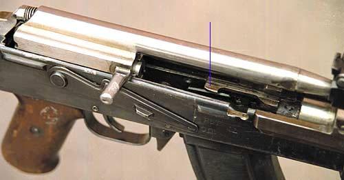 Затвор АК-47 в крайнем заднем положении, возвратная пружина сжата. Стрелкой показан неподвижный отражатель. В АК-47 в полной мере была реализована перспективная концепция компоновки автоматического оружия, главными чертами которой стали компактность, технологичность, простота в обслуживании, изучении и ремонте. И будущих автоматах АКМ, АК74, АК74М легко узнать детали, которые отрабатывались на АК-47
