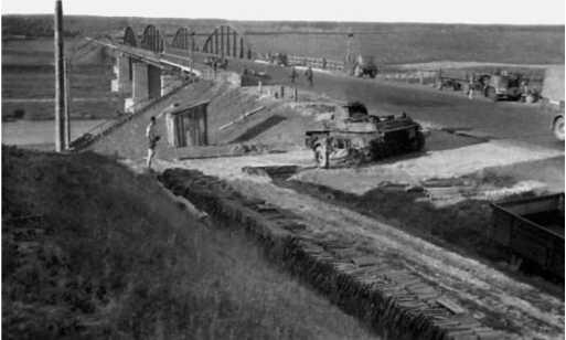 То же место, что и на предыдущих фото, снятое спустя некоторое время. Танк БТ-7М уже сдвинут немцами в сторону, чтобы не мешать проезду. На этом фото хорошо видны не только фермы моста, но и его опоры (ЯМ).