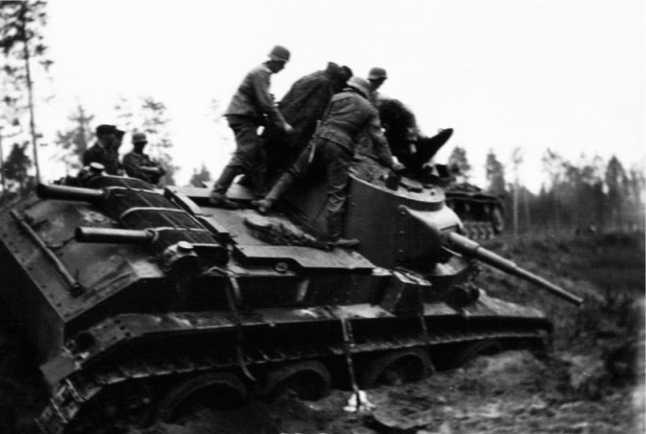 Немецкие солдаты осматривают подбитый танкБТ-7М из состава1-й МосковскойПролетарской дивизии.АвтострадаМосква — Минск, июль 1941 года(АСКМ).