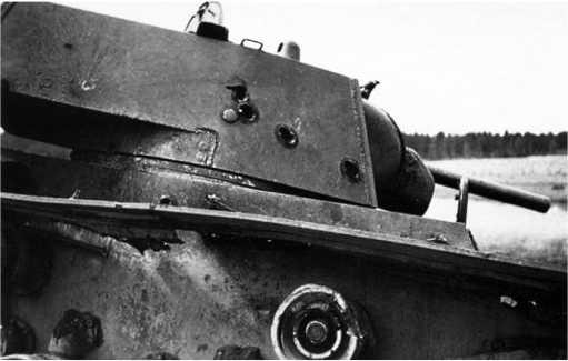 Тот же КВ-1, что и на предыдущем фото — хорошо видно, что по машине велся интенсивный артогонь. Видны следы попадания в башню пяти50-мм снарядов, не пробивших броню (один из них срикошетировал). Еще одно снарядное попадание видно на правом борту корпуса (РГАКФД).