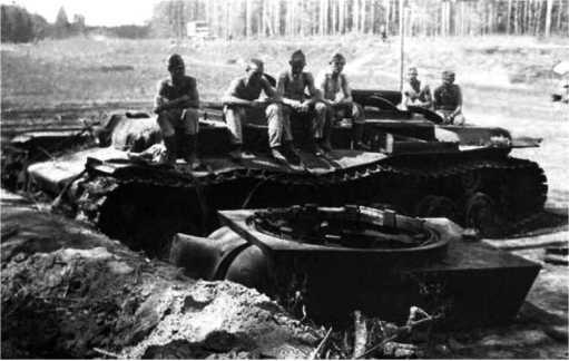 Немецкие солдаты на уничтоженном внутренним взрывом танкеКВ-1 из состава 1-й моторизованной дивизии. Машина находилась у шоссе Москва — Минск (оно видно на заднем плане) на участкеЛошница — Крупки.Июль 1941 года.(ЯМ).