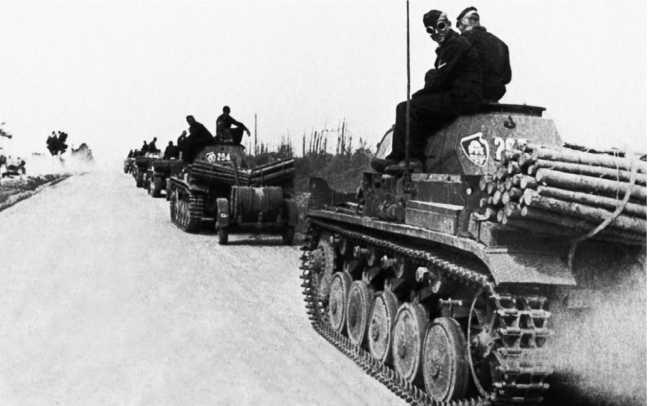 Колонна танков Pz.II из состава18-й танковой дивизии на марше.Июль 1941 года.Передняя машина буксирует прицеп, на котором лежит бочка с горючим — это применялось немцами для повышения запаса хода своих танков. На задней части башен видны эмблемы 18-го танкового полка18-й танковой дивизии.