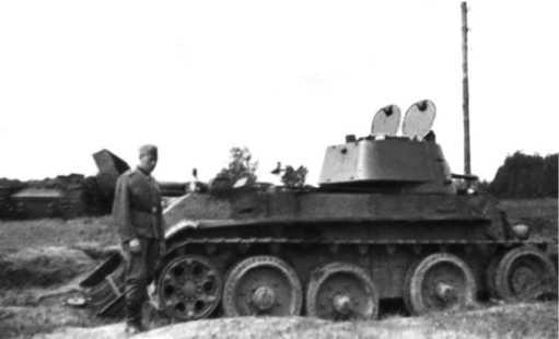 Тот же БТ-7М, что и на предыдущем фото. Июль 1941года. В кормовой части корпуса видна снарядная пробоина, на заднем плане виден уничтоженный танкКВ с сорванной башней.
