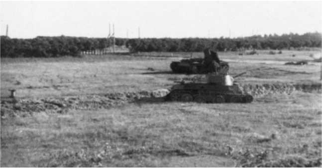 Общий вид поля боя — на переднем плане БТ-7М, изображенный на предыдущих фото, за ним уничтоженный внутренним взрывом КВ-1. Июль1941 года (ЯМ).