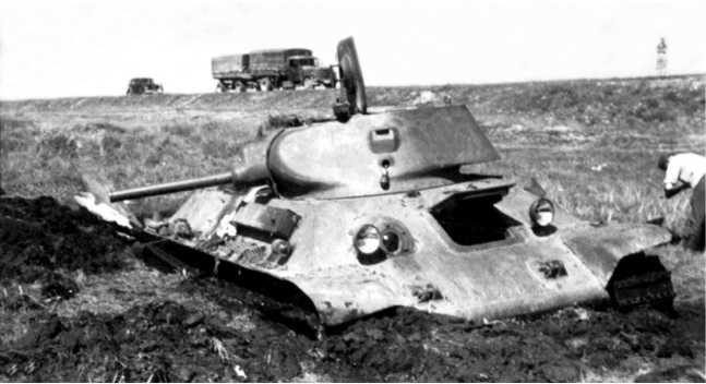 Танк Т-34 с пушкой Л-11 и литой башней. Эта машина находилась дальше всего от шоссе в группе застрявших танков, и впоследствии была вытащена немцами и увезена.Снимок сделан на запад в сторону автострадыМосква — Минск, на котором стоит немецкий грузовик(РГАКФД).