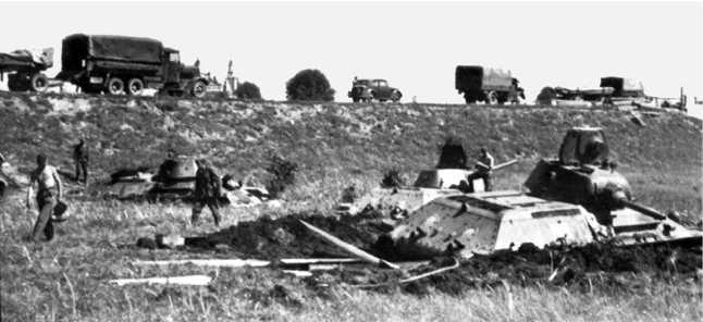 Группа застрявших танков у Толочина: немцы пытаются эвакуировать застрявшую тридцать четверку, под гусеницы засунуты бревна, виден закрепленный буксирный трос. Июль 1941 года (ЯМ).