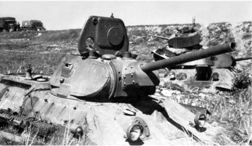 Центральный танк Т-34 группы застрявших танков у Толочина.Машина с пушкойФ-34, за ней видна камуфлированная тридцатьчетверка с Л-11 и Т-26на обочине шоссеМосква — Минск(РГАКФД).