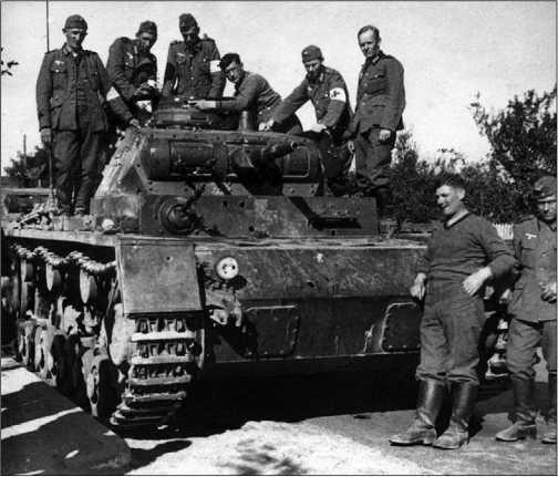 Немецкие солдаты осматривают танк Pz.III Ausf.D, подбитый польской противотанковой артиллерией. На лобовой 14,5-мм броне машины хорошо видны несколько пробоин от 37-мм снарядов. Польша, 1939 год.