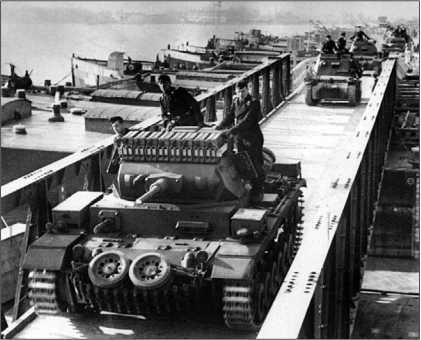 Pz.III Ausf.G проходит по мосту. Обращает на себя внимание способ усиления защиты лобовой части корпуса с помощью запасных гусениц и опорных катков, а также широко практиковавшийся в Вермахте способ перевозки 160 л топлива в канистрах на крыше башни. Балканская кампания, 1941 год.