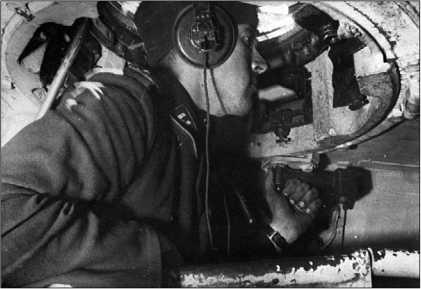 Командир танка ведет наблюдение за местностью через один из перископов командирской башенки.