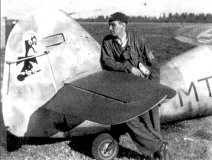 Ас из l/HLeLv-34 стафф-сержант Эрик Лили осматривает только что нарисованную на руле направления его мессершмита новую эмблему эскадрильи в виде орленка. Идея эмблемы принадлежала командиру НLeLv-34, официальна она была одобрена 7 июня 1944г. Лили сбил восемь самолетов противника и совершил 188 боевых вылетов.